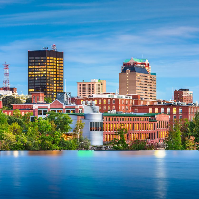 Manchester, New Hampshire, USA Skyline on the Merrimack River at dusk.